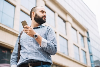 Thoughtful man with phone on urban background