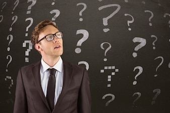 Thoughtful man with question symbols behind