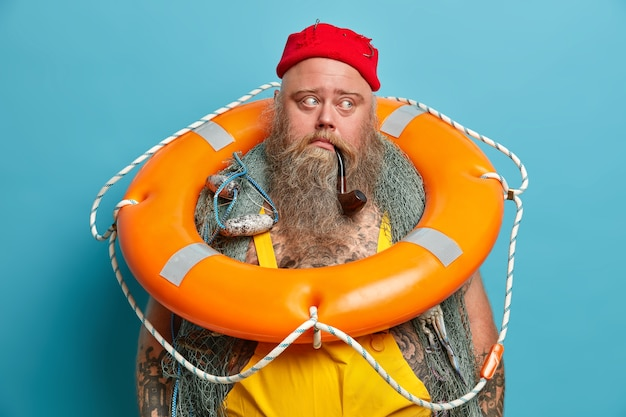 Thoughtful mariner carries inflated ring buoy on neck, ready to rescue people at sea, has thick long beard, smokes pipe