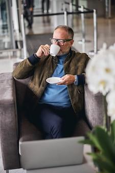Вдумчивый зрелый бизнесмен в очках, пьющий кофе