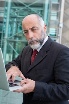 Thoughtful mature man using laptop on street