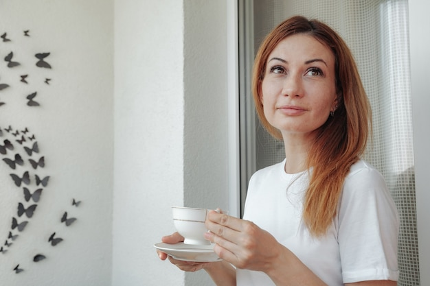 Thoughtful mature woman on balcony of her home with cup of coffee in hands and looking away. middle aged woman drinks morning tea, thinking. concept relax and think while drinking coffee