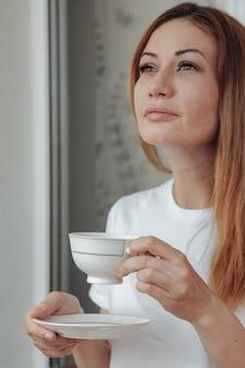 手にコーヒーを片手に目をそらしている彼女の家のバルコニーにいる思いやりのある成熟した女性。中年女性は考えながら朝のお茶を飲みます。コンセプトリラックスしてコーヒーを飲みながら考える