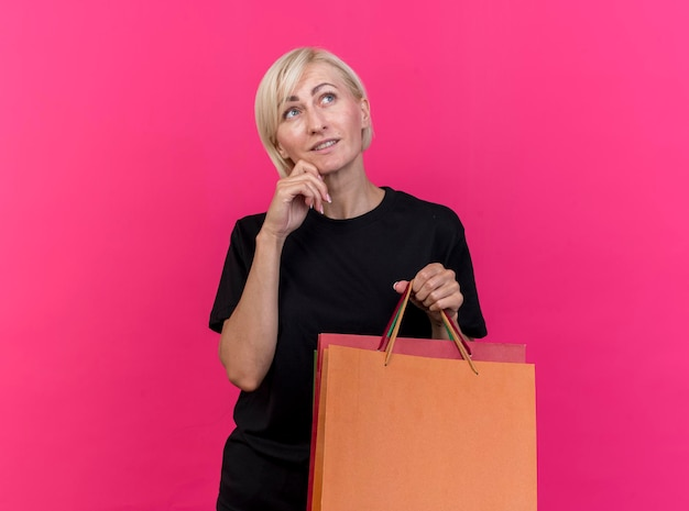 Donna slava bionda premurosa che tiene i sacchetti della spesa toccando il mento che osserva in su isolato sulla parete rosa con lo spazio della copia