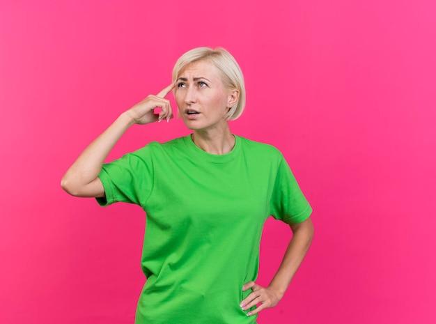 Donna slava bionda di mezza età premurosa che tiene la mano sulla vita che osserva in su facendo pensare il gesto isolato sulla parete rosa con lo spazio della copia
