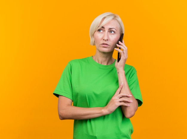 Thoughtful middle-aged blonde slavic woman talking on phone touching arm looking at side isolated on yellow background with copy space