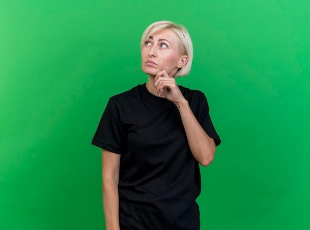 Premurosa donna bionda di mezza età slava toccando il mento cercando isolato su sfondo verde con copia spazio