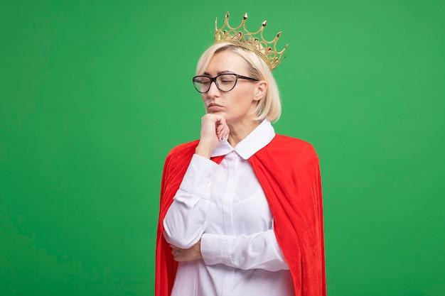 眼鏡と王冠を身に着けている赤いマントの思いやりのある中年の金髪のスーパーヒーローの女性は、コピースペースで緑の壁に隔離されて見下ろしているあごに手を置きます