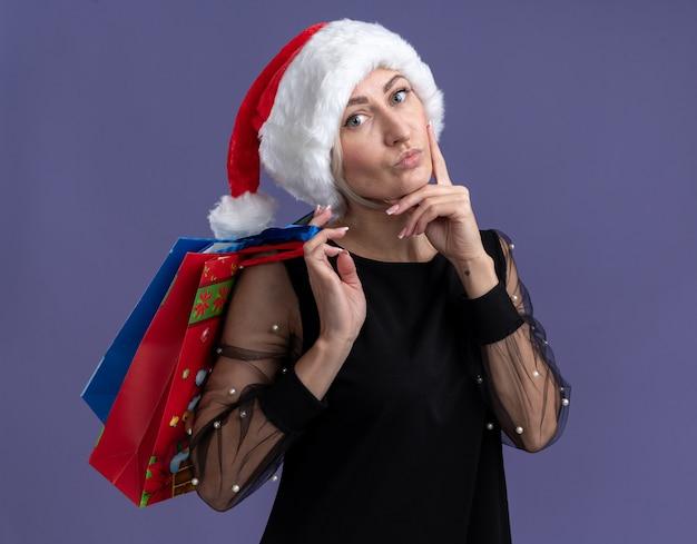 Donna bionda di mezza età premurosa che indossa il cappello di natale che tiene i sacchetti del regalo di natale sulla spalla che sembra toccare il viso isolato sul muro viola