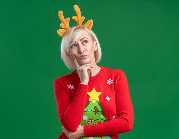 Задумчивая блондинка средних лет в рождественской повязке на голову из оленьих рогов и рождественском свитере смотрит в сторону, держа руку на подбородке, изолированную на зеленом фоне с копией пространства