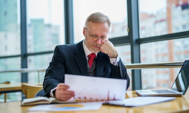 スーツを着た思慮深い中年ビジネスマンが、ノートパソコンをテーブルに置き、書類を扱っている。