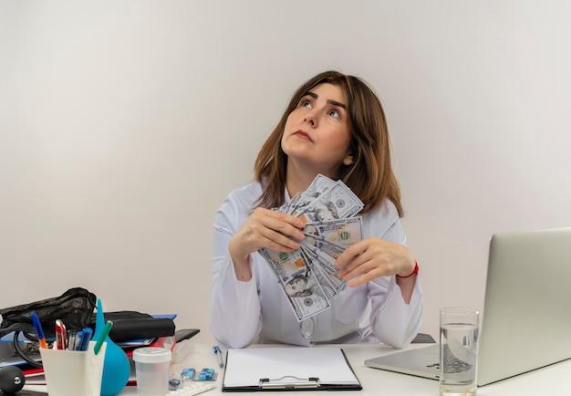 Medico femminile di mezza età premuroso che indossa veste medica e stetoscopio seduto alla scrivania con appunti di strumenti medici e laptop tenendo i soldi guardando in alto isolato