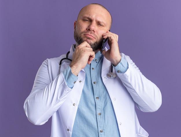 Premuroso medico maschio di mezza età che indossa abito medico e stetoscopio parlando al telefono toccando il mento guardando dritto strizzando gli occhi isolati sul muro viola