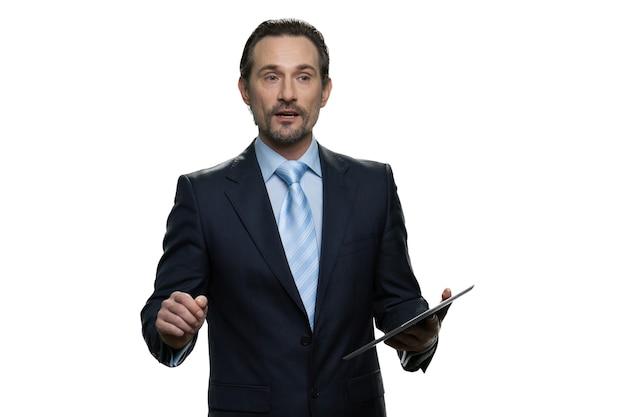 Вдумчивый мужчина средних лет, держащий планшет. портрет умного бизнесмена изолированного на белой стене.
