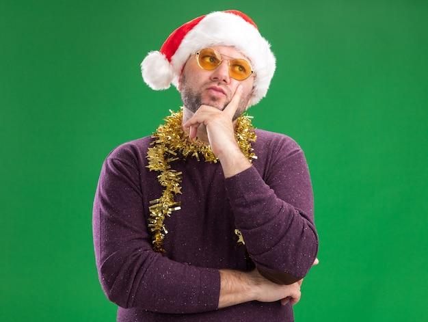 Premuroso uomo di mezza età che indossa un cappello da babbo natale e una ghirlanda di orpelli intorno al collo con gli occhiali tenendo la mano sul mento guardando il lato isolato su sfondo verde con spazio di copia