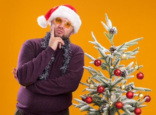 Uomo di mezza età premuroso che indossa cappello da babbo natale e ghirlanda di orpelli intorno al collo con gli occhiali in piedi vicino all'albero di natale decorato tenendo la mano sul mento guardando la telecamera isolata su sfondo arancione