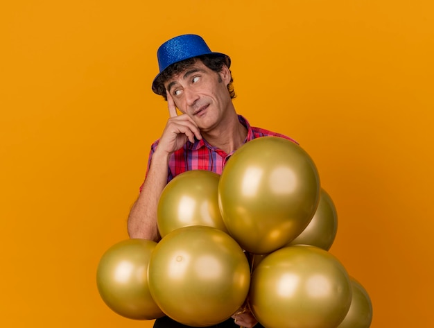 Thoughtful middle-aged party man wearing party hat standing behind balloons putting finger on temple looking at side isolated on orange wall with copy space