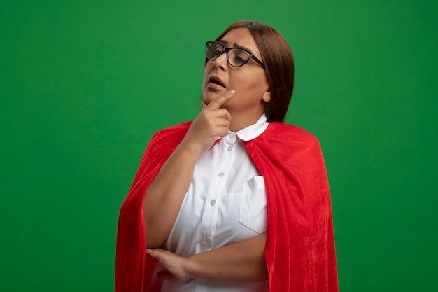 Вдумчивая женщина супергероя средних лет смотрит в сторону в очках, положив руку под подбородок, изолированную на зеленом