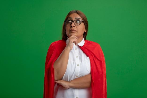Вдумчивый супергерой среднего возраста женщина в очках, положив руку под подбородок, изолированную на зеленом