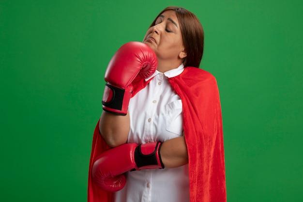 Premurosa donna di mezza età supereroe con gli occhi chiusi che indossa guanti da boxe mettendo la mano sotto il mento isolato sul verde