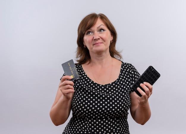 孤立した白い壁にカードと携帯電話を保持している思いやりのある中年女性