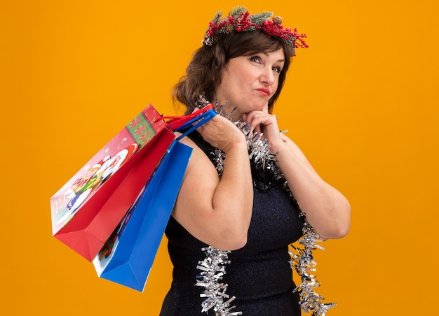 크리스마스 선물 가방을 들고 프로필보기에 서있는 목 주위에 크리스마스 머리 화환과 반짝이 갈 랜드를 입고 사려 깊은 중년 여성
