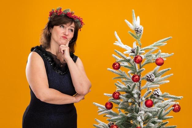 Задумчивая женщина средних лет в рождественском венке на голове и гирлянде из мишуры на шее стоит возле украшенной елки