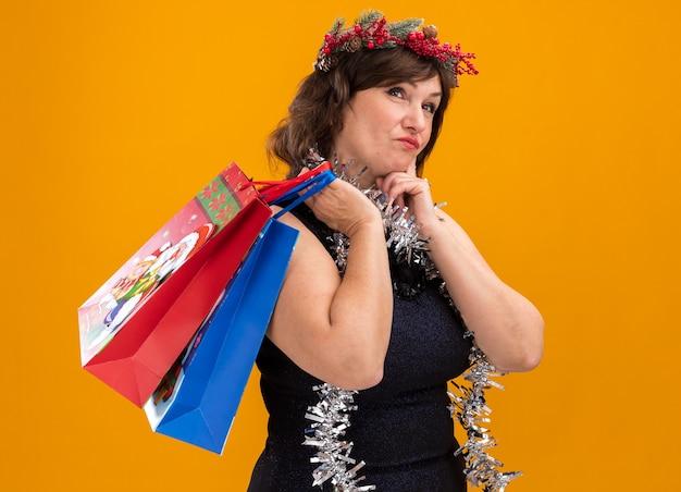 Premurosa donna di mezza età che indossa la testa di natale ghirlanda e tinsel ghirlanda intorno al collo in piedi in vista di profilo tenendo il regalo di natale sacchetti