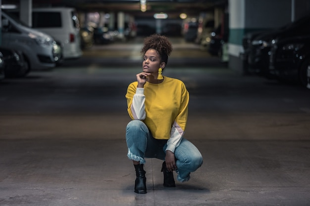 Thoughtful millennial black woman in trendy outfit in underground parking