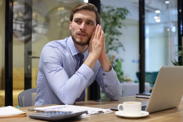 Вдумчивый современный деловой человек, работающий с ноутбуком, сидя в офисе.
