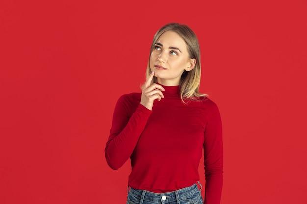 思いやりがある。赤い壁に分離された若い白人金髪女性のモノクロの肖像画。シャツの美しい女性モデル。人間の感情、顔の表情、販売、広告のコンセプト。若者文化。 無料写真