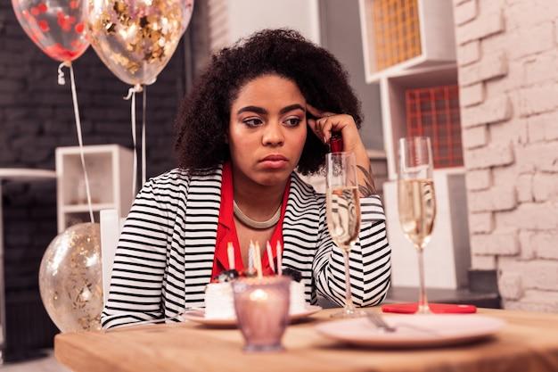사려 깊은 분위기. 생일 케이크 앞에 앉아있는 동안 그녀의 외로움에 대해 생각하는 우울한 우울한 여자