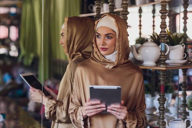 デジタルタブレットを見ている思いやりのあるイスラム教徒の女性