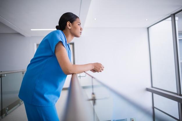 Вдумчивый медсестра, опираясь на перила
