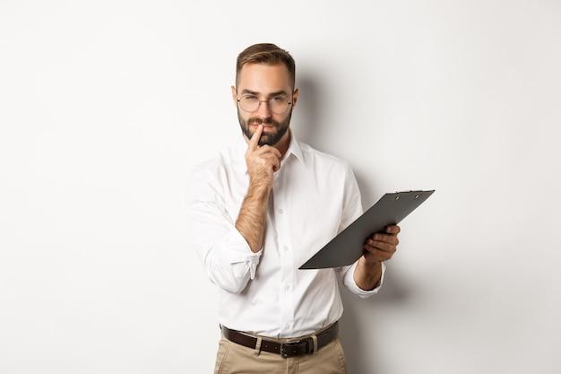 思いやりのあるオフィスの従業員は、クリップボードにドキュメントを保持し、考え、白い背景の上に立って働いています。