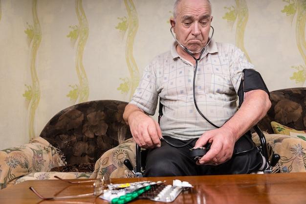 혈압 장치가 있는 사려 깊은 노인, 테이블 위에 약을 들고 거실에서 휠체어에 앉아 있습니다.