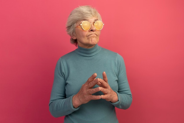 Premurosa vecchia donna che indossa un maglione blu a collo alto e occhiali da sole che tiene le mani insieme guardando in alto