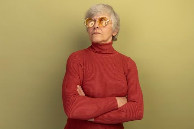 Premurosa vecchia donna che indossa un maglione a collo alto rosso e occhiali da sole in piedi con postura chiusa guardando in alto isolato su parete verde oliva con spazio copia