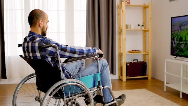 テレビを見ている車椅子の思慮深い麻痺した男。