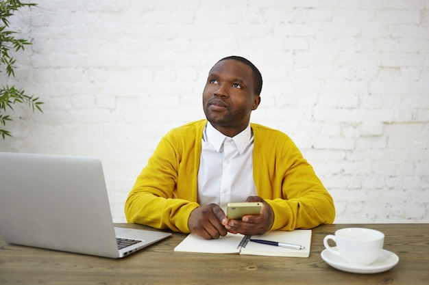 Thoughtful pensive african male freelancer in stylish clothes looking up with thoughtful expression, using smart phone, calculating finances, working at home office, sitting in front of open laptop