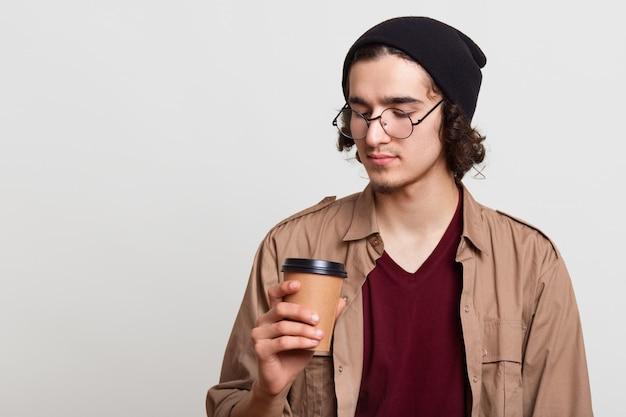 Yougster pensieroso premuroso che ha papercup di caffè, tenendo la bevanda calda in una mano, guardandolo attentamente, in posa isolato su grigio chiaro, essendo in pausa. concetto di gioventù.