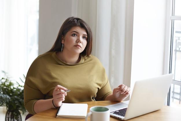 思いやりのある物思いにふける若いぽっちゃり女性ジャーナリストは、ポータブルコンピューター、マグカップを持って机に座って、コピーブックにメモを書きながら見上げ、遠くで働き、オンラインマガジンの新しい記事を書いています