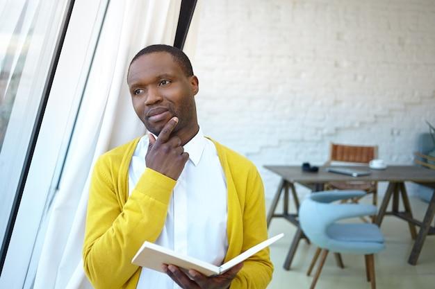 あごに触れ、オフィスのインテリアに立って、窓越しに見て、日を計画し、日記を持っている思いやりのある物思いにふける若い暗い肌のビジネスマン。人、ビジネス、仕事、職業の概念