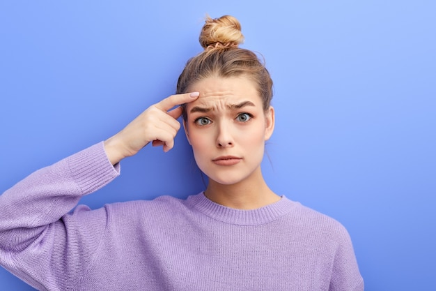 Thoughtful pensive young girl with hair bun making displeased grimace as if saying no