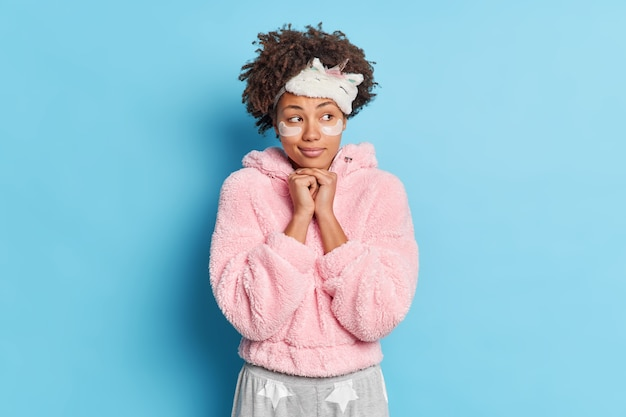 Thoughtful pleasant looking curly woman keeps hands under chin has ideas imagines something dressed in sleepwear applies beauty pads for skin care isolated over blue wall prepares for sleep