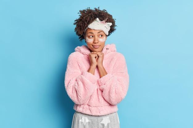 思いやりのある気持ちの良い巻き毛の女性が手をあごの下に置いているアイデアは、寝間着を着た何かが青い壁に隔離されたスキンケアのための美容パッドを適用して睡眠の準備をすることを想像しています