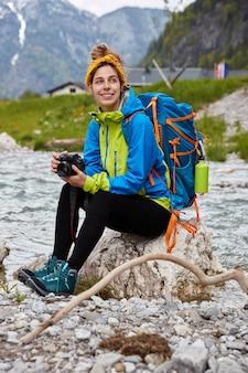 Вдумчивый довольный турист принимает участие в приключениях, активно отдыхает в горах, позирует на камне у ручья.