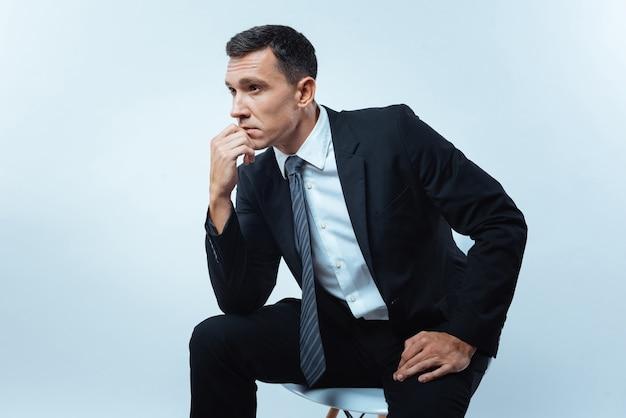 思いやりのあるポーズ。椅子に座って、彼の仕事について考えている間彼のあごを持っている素敵な思慮深い賢い人