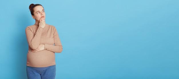 사려 깊은 임산부는 신중하게 옆으로 보이고 턱에 손을 대고 출산 계획을 세우고 파란색 벽에 고립 된 베이지 색 스웨터와 청바지를 입고 어머니가되기를 꿈꿉니다.
