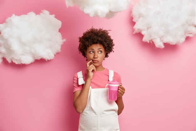 Thoughtful pregnant woman looks thoughtfully aside, makes planning about child birth, dreams to become mother, dressed in clothes for future moms, drinks water isolated on pink wall white clouds